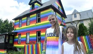 Taylor Berg and her son Mattix Berg, 10, pose in front of their rainbow colored home at 1625 9th Ave, Friday, July 17, 2020 in Moline, Ill. Moline city officials said Thursday in a hand-delivered letter to Taylor Berg that she does not have to paint over the broad purple, blue, green, yellow, orange and red horizontal stripes that run top to bottom down her two-story wood-frame house, the Quad-City Times reported. (Gary L. Krambeck/The Rock Island Argus via AP)