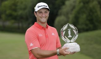 Jon Rahm, of Spain, poses with the trophy after winning the Memorial golf tournament, Sunday, July 19, 2020, in Dublin, Ohio. (AP Photo/Darron Cummings)