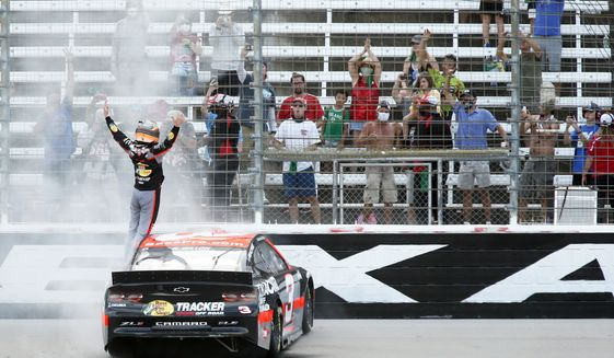 Austin Dillon stands on his car in the front stretch after winning a NASCAR Cup Series auto race at Texas Motor Speedway in Fort Worth, Texas, Sunday, July 19, 2020. (AP Photo/Ray Carlin)