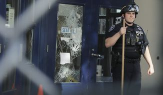 A Seattle Police officer holds a broom as he cleans up broken glass outside the East Precinct Building, Sunday, July 19, 2020 in Seattle. Protesters broke windows at the building earlier in the afternoon. (AP Photo/Ted S. Warren)