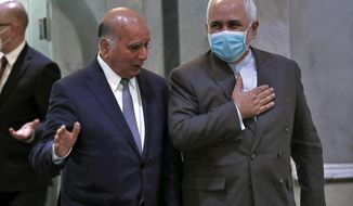 Iranian Foreign Minister, Mohammad Javad Zarif, right, wears a mask to help prevent the spread of the coronavirus walks with his Iraqi counterpart, Fouad Hussein during his visit to Baghdad, Iraq, Sunday, July 19, 2020. (AP Photo/Hadi Mizban)