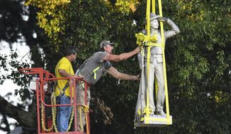The Confederate statue located in the Circle at the University of Mississippi is lowered to the ground as part of the process to move it to the Confederate Soldiers Cemetery on campus in Oxford, Miss. Tuesday, July 14, 2020.  (AP Photo/Bruce Newman) ** FILE **