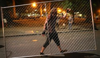 Protesters relocate a fence in front of the Justice Center, Saturday, July 18, 2020, during another night of protests in Portland, Ore. (Mark Graves/The Oregonian via AP)