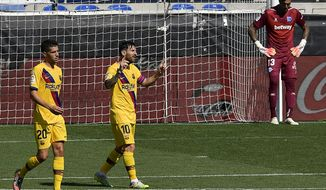Barcelona's Lionel Messi, center, celebrates his goal against Alaves during the Spanish La Liga soccer match between Alaves and FC Barcelona, at Mendizorroza stadium, in Vitoria, northern Spain, Sunday, July 19, 2020. (AP Photo/Alvaro Barrientos)