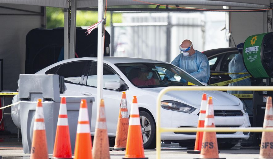 Citizens are tested by healthcare workers at the COVID-19 drive-thru testing center at Hard Rock Stadium in Miami Gardens as the coronavirus pandemic continues on Sunday, July 19, 2020. (David Santiago/Miami Herald via AP)