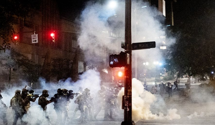 Federal agents use crowd control munitions to disperse Black Lives Matter protesters near the Mark O. Hatfield United States Courthouse on Monday, July 20, 2020, in Portland, Ore. Officers used teargas and projectiles to move the crowd after some protesters tore down a fence fronting the courthouse. (AP Photo/Noah Berger)