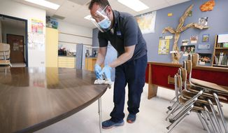 Des Moines Public Schools custodian Joel Cruz cleans a desk in a classroom at Brubaker Elementary School, Wednesday, July 8, 2020, in Des Moines, Iowa. School districts that plan to reopen classrooms in the fall are wrestling with whether to require teachers and students to wear face masks. In Iowa, among other places, where Democratic-leaning cities like Des Moines and Iowa City have required masks to curb the spread of the coronavirus, while smaller, more conservative communities have left the decision to parents. (AP Photo/Charlie Neibergall)  **FILE**