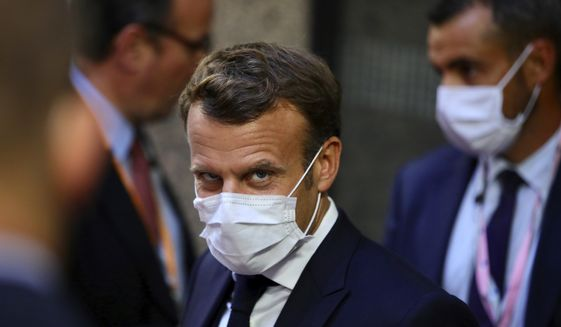 French President Emmanuel Macron, center, leaves the European Council building in the early morning during an EU summit in Brussels, Monday, July 20, 2020. Leaders from 27 European Union nations met throughout the night Sunday to assess an overall budget and recovery package spread over seven years estimated at some 1.75 trillion to 1.85 trillion euros. The summit will continue into its fourth day on Monday. (AP Photo/Olivier Matthys, Pool)