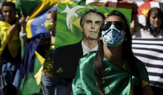 People show their support for Brazil's President Jair Bolsonaro during a demonstration in Brasilia, Brazil, Sunday, July 19, 2020. Last week, Bolsonaro announced for the second time that he has tested positive for the new coronavirus, while the federal health ministry reported that the country had passed 2 million confirmed cases of virus infections and more than 76,000 deaths. (AP Photo/Eraldo Peres)