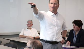 """FILE - In this Aug. 26, 2019 file photo, U.S. Rep. Steve Watkins, R-Kan., makes a point during a town hall meeting in Topeka, Kan. Watkins, a freshman congressman facing felony criminal charges over previously listing a UPS Inc. postal box as his residence on a state voter registration form, is stepping down temporarily from his House committee assignments. Watkins said Friday, July 17, 2020 that he is """"temporarily and voluntarily"""" leaving the three committees on which he serves. House Republican conference's rules require members facing a potential felony conviction to leave their committee posts.  (AP Photo/John Hanna File)"""