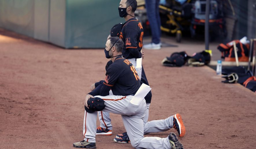 San Francisco Giants' manager Gabe Kapler kneels during the national anthem prior to an exhibition baseball game against the Oakland Athletics, Monday, July 20, 2020, in Oakland, Calif. (AP Photo/Ben Margot)
