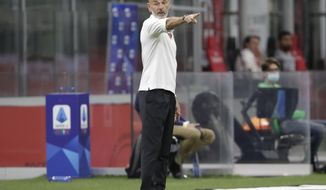 AC Milan's manager Stefano Pioli gives instructions to his players during a Serie A soccer match between AC Milan and Bologna, at the San Siro stadium in Milan, Italy, Saturday, July 18, 2020. (AP Photo/Luca Bruno)
