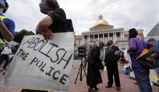 People gather for a protest outside the Statehouse, Monday, July 20, 2020, in Boston, on a day when thousands across the country planned to walked off the job to protest systemic racism and economic inequality that has worsened during the coronavirus pandemic. (AP Photo/Charles Krupa)