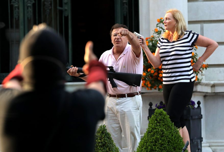 In this June 28, 2020 file photo, armed homeowners Mark and Patricia McCloskey, standing in front their house along Portland Place confront protesters marching to St. Louis Mayor Lyda Krewson's house in the Central West End of St. Louis. St. Louis' top prosecutor told The Associated Press on Monday, July 20, 2020 that she is charging a white husband and wife with felony unlawful use of a weapon for displaying guns during a racial injustice protest outside their mansion. (Laurie Skrivan/St. Louis Post-Dispatch via AP File)