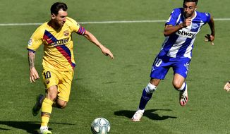 Barcelona's Lionel Messi, left, fights for the ball with Alaves' Victor Camarasa during the Spanish La Liga soccer match between Alaves and FC Barcelona, at Mendizorroza stadium, in Vitoria, northern Spain, Sunday, July 19, 2020. (AP Photo/Alvaro Barrientos)