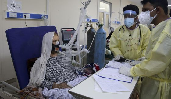 Afghan doctors help a patient to breathe through an oxygen mask in the Intensive Care Unit ward for COVID-19 patients at the Afghan-Japan Communicable Disease Hospital in Kabul, Afghanistan, Tuesday June 30, 2020. (AP Photo/Rahmat Gul)