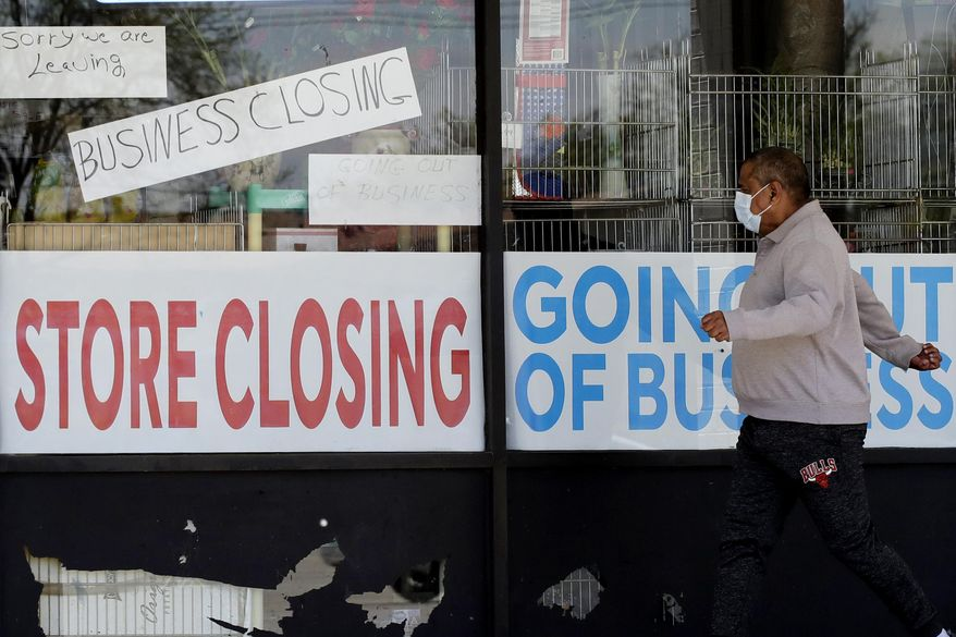 In this Thursday, May 21, 2020, file photo, a man looks at signs of a closed store due to the coronavirus pandemic, in Niles, Ill. State governments are pushing for help from Congress to fix budget gaps caused by the coronavirus pandemic and economic shutdowns. (AP Photo/Nam Y. Huh, File)