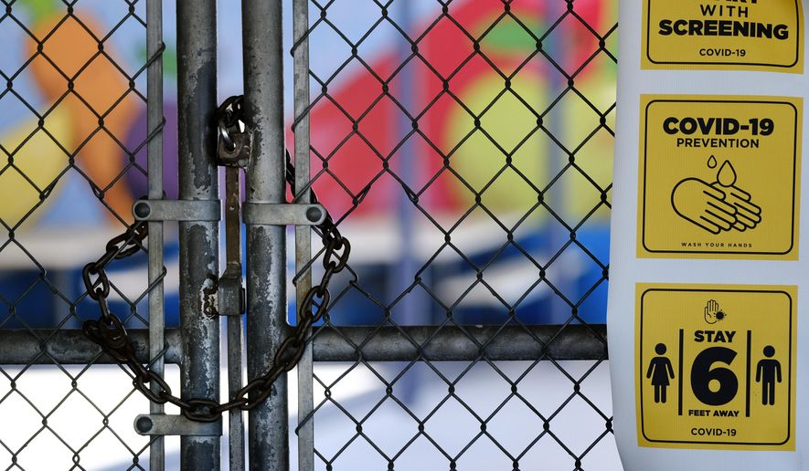 In this July 13, 2020, file photo, a chain-link fence lock is seen on a gate at a closed Ranchito Elementary School in the San Fernando Valley section of Los Angeles. States are furloughing workers, borrowing billions, delaying construction projects and reducing aid to local governments and schools as ways to cope in response to revenue drops that are expected to top 20% in some states, amid the coronavirus pandemic. (AP Photo/Richard Vogel, File)