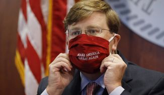 "Mississippi Gov. Tate Reeves adjusts his ""Make America Great Again,"" face mask upon concluding his press briefing with members of the state's COVID-19 response team, to discuss the ongoing strategy to reduce and limit transmission, Monday, July 20, 2020, in Jackson, Miss. (AP Photo/Rogelio V. Solis)"