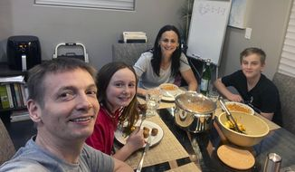 In this May 20, 2020, photo provided by the Chicago Sky, Phoenix Mercury WNBA coach Sandy Brondello, rear, her husband Olaf Lange, left, an assistant coach for the WNBA Chicago Sky, and their children Brody, right, and Jayda eat at home in Phoenix, Ariz., while quarantining. The Brondello family is in the bubble in Bradenton, Fla. Sandy and Jayda are living in a hotel room while Olaf and Brody are in a villa on the IMG Academy property. There are no league rules preventing the couple to stay together with their two children but the coaches decided against it to maintain a level of professionalism. (Olaf Lange via AP)