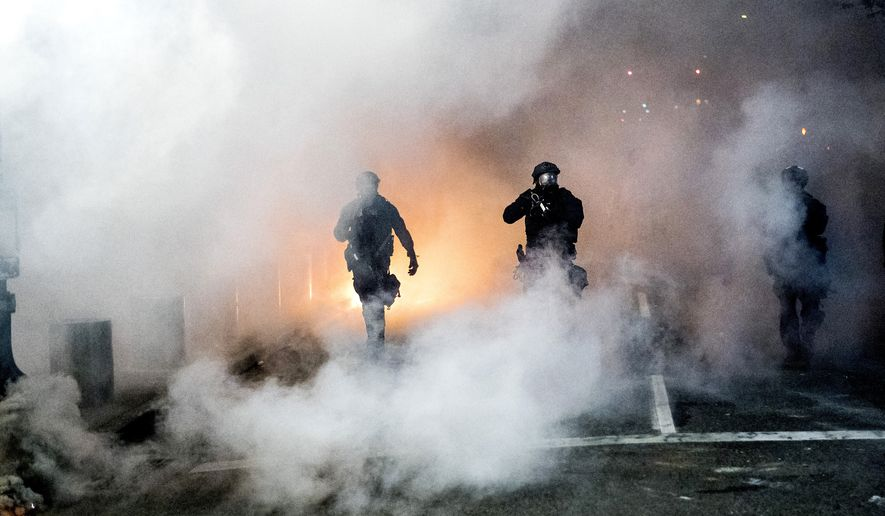 Federal officers use crowd control munitions to disperse Black Lives Matter protesters outside the Mark O. Hatfield United States Courthouse on Tuesday, July 21, 2020, in Portland, Ore. (AP Photo/Noah Berger)