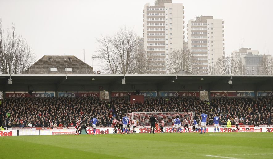 FILE - In this Saturday, Jan. 25, 2020 file photo, spectators watch from the stands of Griffin Park stadium, inaugurated in 1904, during the English FA Cup fourth round soccer match between Brentford FC and Leicester City at Griffin Park stadium in London. With another win at home on Wednesday July 21, 2020, west London club Brentford could end up saying goodbye to its 116-year-old stadium and hello to the Premier League for the first time. (AP Photo/Kirsty Wigglesworth, File)