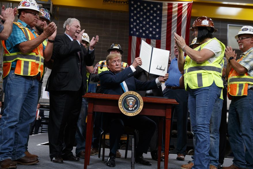 FILE - In this April 10, 2019, file photo, President Donald Trump holds up an executive order on energy and infrastructure after signing it at the International Union of Operating Engineers International Training and Education Center in Crosby, Texas. Attorneys general in 20 states and the District of Columbia sued the Trump administration on Tuesday, July 21, 2020, alleging that new federal rules undermine their ability to protect rivers, lakes and streams within their borders. President Trump in April 2019 issued an executive order directing the change that critics said could make it harder for states to block pipelines and other projects over concerns that they could impair water quality. (AP Photo/Evan Vucci, File)