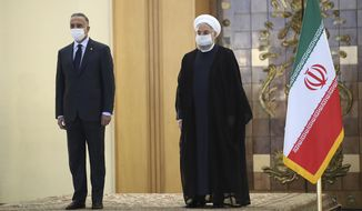 In this photo released by the official website of the office of the Iranian Presidency, President Hassan Rouhani, right, welcomes Iraqi Prime Minister Mustafa al-Kadhimi as they wear protective face masks to help prevent spread of the coronavirus, during an official arrival ceremony, in Tehran, Iran, Tuesday, July 21, 2020. (Iranian Presidency Office via AP)