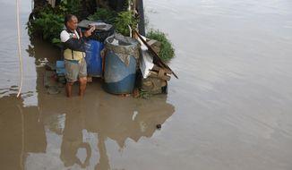 A Nepalese man takes photos of flooded Bagmati river following heavy monsoon rains in Kathmandu, Nepal, Monday, July 20, 2020. The weather department has has forecast heavy rains this week. (AP Photo/NIranjan Shrestha)