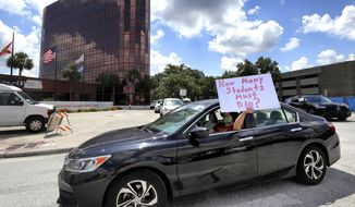 In this Tuesday, July 7, 2020, file photo, a teacher holds up a sign while driving by the Orange County Public Schools headquarters as educators protest in a car parade around the administration center in downtown Orlando, Fla. Teachers unions have begun pushing back on what they see as unnecessarily aggressive timetables for reopening. (Joe Burbank/Orlando Sentinel via AP, File)