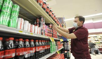 Store manager Donny Price restocks cans of Coke on the shelves at Gerrity's in Hanover Township, Pa., Tuesday, July 14, 2020. Area shoppers are encountering challenges getting certain soda and beer brands because of a national aluminum can shortage. Coca-Cola, for example, isn't producing 12-packs of cans of its Minute Maid Light Lemonade so it can meet the high demand of its more popular brands like Coca-Cola and Sprite as more people have been buying canned beverages during the COVID-19 pandemic. (Mark Moran/The Citizens' Voice via AP)