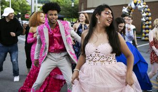 In this June 23, 2020, photo, Steel Valley High School students dance at their prom at the Waterfront Shopping Center in Homestead, Pa., organized by one of the student's father after the school's prom was canceled amid the coronavirus pandemic. Amid the debate over how to reopen schools safely, some teens and parents are organizing private proms to replace events canceled because of the coronavirus. (Lily LaRegina/Pittsburgh Post-Gazette via AP) **FILE**