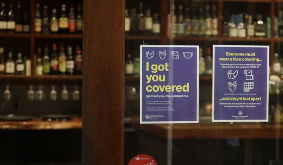 Signs advising social distancing and wearing face masks are posted on a door of The Barrel Room restaurant during the coronavirus outbreak in San Francisco, Tuesday, July 14, 2020. The Barrel Room, a San Francisco wine bar and restaurant, cautiously reopened last week, hoping to salvage as much of 2020 as possible from the coronavirus pandemic and the lockdowns meant to contain it. (AP Photo/Jeff Chiu) ** FILE **