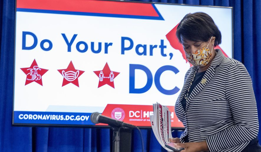 District of Columbia Mayor Muriel Bowser wears a face mask to protect against the spread of the coronavirus outbreak, as she leaves a news conference on the coronavirus and the District's response, Monday, July 20, 2020 in Washington.  In the face of newly rising infection numbers, Bowser says she'll issue an executive order making face masks mandatory outside the home. (AP Photo/Andrew Harnik)