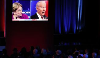FILE - In this Feb. 19, 2020, file photo guests watch Democratic presidential candidates, Sen. Elizabeth Warren, D-Mass., and former Vice President Joe Biden speak on a big screen during a Democratic presidential primary debate in Las Vegas, hosted by NBC News and MSNBC. Warren, a Massachusetts senator and leading progressive, has become an unlikely confidant and adviser to Biden, the presumptive Democratic presidential nominee. They talk every 10 days or so, according to aides to both politicians who requested anonymity to describe their relationship. (AP Photo/John Locher, File)