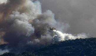 A firefighting plane drops water on a hill side, near the seaside area Kechries, near Corinth, Greece, on Wednesday, July 22, 2020. Homes have been evacuated at three sites near the southern Greek city of Cornith as firefighters struggled to contain a hillside blaze. (AP Photo/Petros Giannakouris)