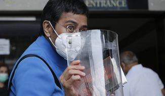 Rappler CEO and Executive Editor Maria Ressa shows her face shield as she arrives at the Pasig Regional Trial Court to attend an arraignment related to tax evasion charges filed against her in Pasig, Metro Manila, Philippines on Wednesday, July 22, 2020. (AP Photo/Aaron Favila)