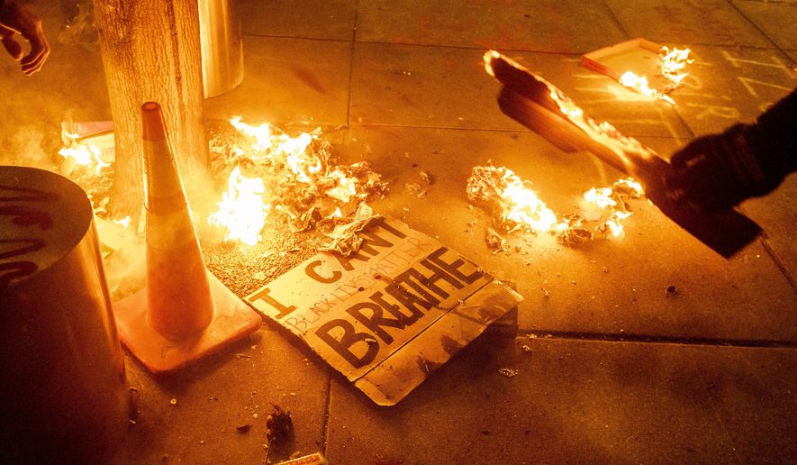 A Black Lives Matter protester burns a sign outside the Mark O. Hatfield United States Courthouse on July 21, 2020, in Portland, Ore. (AP Photo/Noah Berger)