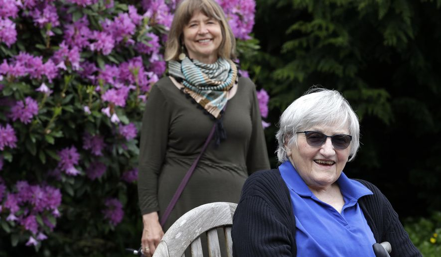 Jessie Cornwell, a resident of the Ida Culver House Ravenna, right, poses for a photo with the Rev. Jane Pauw, in Seattle on May 21, 2020. Cornwell tested positive for the coronavirus but never became ill, and may have been infectious when she shared a ride to Bible study with Pauw, who later got sick with COVID-19. (AP Photo/Elaine Thompson)