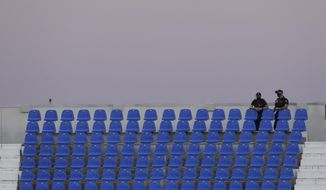Spanish police officers, standing on empty stands and wearing face masks to protect from the spread of coronavirus, watch the Spanish La Liga soccer match between Leganes and Real Madrid at the Butarque Stadium in Leganes, on the outskirts of Madrid, Spain, Sunday, July 19, 2020. (AP Photo/Bernat Armangue)