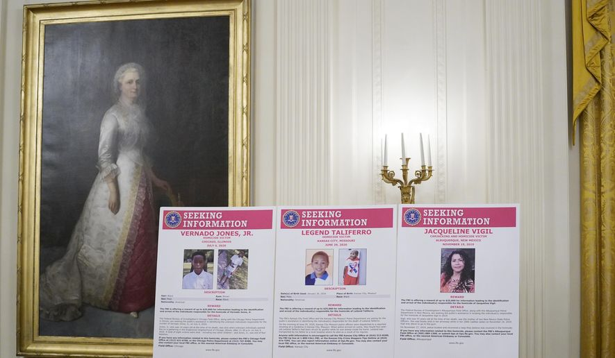 """A portrait of first lady Martha Washington over looks a display of seeking information posters for Vernado Jones Jr., Legend Taliferro and Jacqueline Vigil during an event on """"Operation Legend: Combatting Violent Crime in American Cities,"""" in the East Room of the White House, Wednesday, July 22, 2020, in Washington. (AP Photo/Evan Vucci)"""