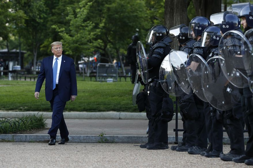 FILE - In this June 1, 2020, file photo President Donald Trump walks past police in Lafayette Park after visiting outside St. John's Church across from the White House in Washington.  When it comes to squelching protests in Democrat-run cities, Trump is eager to send in federal troops and agents — even when local leaders are begging him to butt out. (AP Photo/Patrick Semansky, File)