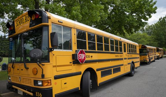 Fairfax County Public School buses parked at a middle school in Falls Church, Va., Monday, July 20, 2020. (AP Photo/J. Scott Applewhite) ** FILE **
