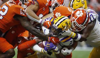 FILE - In this Jan. 13, 2020, file photo, LSU wide receiver Justin Jefferson (2) is tackled by Clemson during the first half of an NCAA College Football Playoff national championship game in New Orleans. The NCAA's latest guidance for playing college sports during the COVID-19 pandemic recommends testing players once a week within 72 hours of competition. For typical Saturday football games, that means Wednesday would be the soonest athletes would be tested.Is that enough for a team of about 100 athletes playing a contact sport to get through a season without major disruptions? Especially, considering simply being exposed to someone who tests positive can land an athlete in quarantine for two weeks? (AP Photo/Gerald Herbert, File)