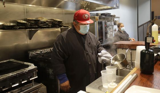 Jose Peraza, sous chef at The Barrel Room, wears a mask while working at the restaurant in San Francisco, Tuesday, July 14, 2020. The Barrel Room, a San Francisco wine bar and restaurant, cautiously reopened this month, hoping to salvage as much of 2020 as possible from the coronavirus pandemic and the lockdowns meant to contain it. (AP Photo/Jeff Chiu)