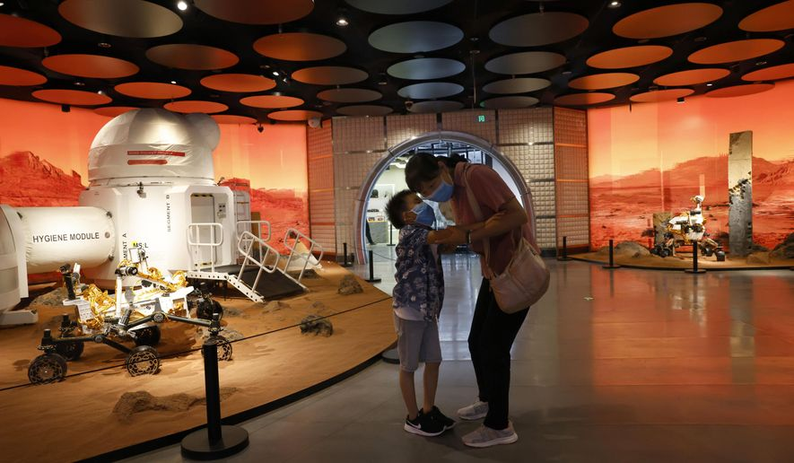 A child whispers to a woman as they visit an exhibition depicting rovers and bio-domes in Mars, in Beijing Thursday, July 23, 2020. China is expected to launch a rover to Mars in one of three missions to the red planet, one from the U.S. and another by the United Arab Emirates. (AP Photo/Ng Han Guan)