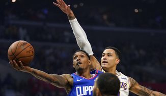 FILE - In this March 8, 2020, file photo, Los Angeles Clippers guard Lou Williams, left, shoots as Los Angeles Lakers forward Kyle Kuzma defends during the first half of an NBA basketball game in Los Angeles. (AP Photo/Mark J. Terrill, File)