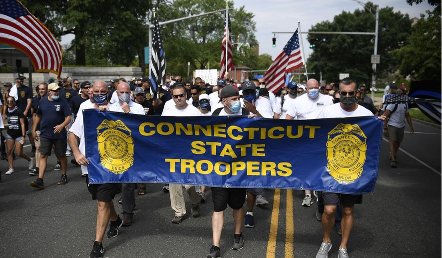 """People participating in a """"Back the Blue"""" rally to show support for law enforcement officers march toward the State Capitol, Thursday, July 23, 2020, in Hartford, Conn. (AP Photo/Jessica Hill)"""