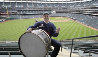 FILE - In this April 27, 2011, file photo, Cleveland Indians fan John Adams poses in his usual centerfield bleacher seat with his ever-present bass drum before a baseball game between the Indians and the Kansas City Royals in Cleveland. Adams, who will miss his first home opener since 1955 on Friday due to the coronavirus, has been keeping the beat for the Indians since 1973.  AP Photo/Amy Sancetta, File)