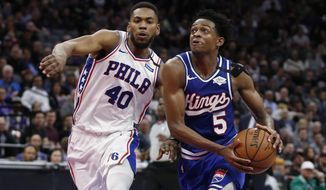 FILE - In this Thursday, March 5, 2020, file photo, Sacramento Kings guard De'Aaron Fox, right, drives to the basket as Philadelphia 76ers forward Glenn Robinson III defends during the second half of an NBA basketball game in Sacramento, Calif. Fox is nursing a sprained ankle and his status for the restart of the NBA basketball season amid the coronavirus pandemic remains up in the air. (AP Photo/Rich Pedroncelli, File)
